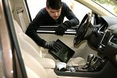 pic of stealing  - Man burglar steals the tablet of car - JPG