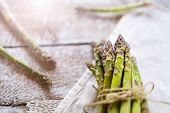 foto of spears  - Bunch of fresh green asparagus spears tied with twine on a rustic wooden table - JPG