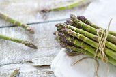 picture of spears  - Bunch of fresh green asparagus spears tied with twine on a rustic wooden table - JPG