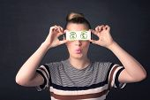 stock photo of gril  - Young girl holding paper with green dollar sign concept - JPG