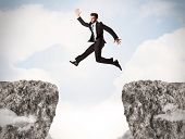 stock photo of gap  - Funny business man jumping over rocks with gap concept - JPG