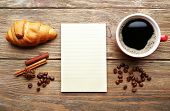 stock photo of croissant  - Cup of coffee with fresh croissant and blank sheet of paper on wooden table - JPG