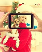 foto of christmas dog  - child in Christmas clothes holding his dog and posing for a photograph