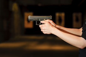 stock photo of shooting-range  - a female police officer pointing her gun at in a firing range - JPG