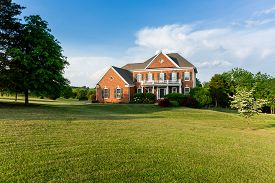 stock photo of in front  - Front of home and garage of large single family modern US house with landscaped gardens and lawn on a warm sunny summers day - JPG
