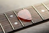 Guitar Frets With Mediator On Strings poster