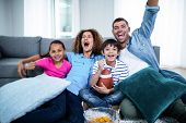 Family watching american football match on television at home poster