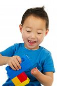foto of physically handicapped  - Happy Chinese boy with light handicap is playing with colorful blocs - JPG