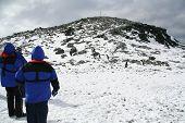 Blue Parka Tourists Climbing A Hill poster