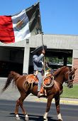 image of vaquero  - vaquero on horseback with Mexican flag - JPG