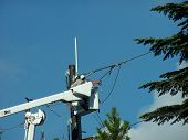 pic of cherry-picker  - two power line workers in white cherry picker work on lines - JPG