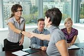 image of conduction  - Panel of business people sitting at table in meeting room conducting job interview greeting female applicant - JPG