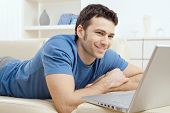 stock photo of belly-band  - Happy young man laying on sofa and using laptop computer at home - JPG
