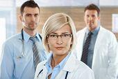 Постер, плакат: Медицинская команда на женский врач больницы коридор в передней глядя на камеру улыбаясь