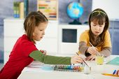 Elementary age children sitting around desk enjoying painting with colors in art class at primary sc
