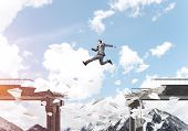 Businessman Jumping Over Gap In Bridge Among Flying Paper Planes As Symbol Of Overcoming Challenges. poster