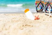 Protective Sunscreen Or Sunblock And Sunbath Lotion In White Plastic Bottles With Sandals On Tropica poster