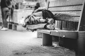 Poor Homeless Man Or Refugee Sleeping On The Wooden Bench On The Urban Street In The City, Social Do poster