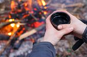 Man Hands Holding Mug From Thermos Near The Fire Outdoors.traveler Drinking Tea From Mug At Camp poster