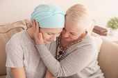 Mature woman visiting her daughter with cancer indoors poster