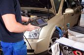 foto of internal combustion  - Detail of a mechanic with an electronic engine diagnostics tool - JPG