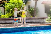 Kids Play With Water Hose At Swimming Pool. poster
