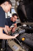 stock photo of auto repair shop  - A team of mechanics using an electronic diagnostics tool - JPG