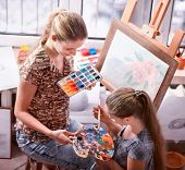 Artist painting easel in studio. Authentic children girl paints with set palette watercolor paints p poster