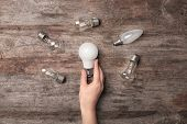 Woman holding LED lamp near incandescent light bulbs on wooden background poster