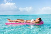 Luxury summer vacation beach woman relaxing lying down on inflatable pool float floating on turquois poster