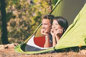 Two young people relaxing in camping tent in summer outdoors nature mountains forest. Happy couple t poster