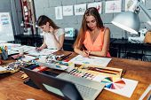 Designers Workspace. Two Female Artists Drawing Decorative Elements Sitting At Desk In Creative Stud poster