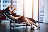 Fashion Model With Slim Long Legs Wearing Black Cocktail Dress Lying On Lounge Chair In Penthouse Ap poster