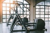 Close Up View Of Elliptical Fitness Crosstrainer Machines In Fitness Center. Perfect For Any Fitness poster