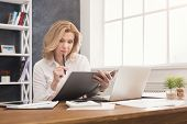Thoughtful Successful Businesswoman In Formal Wear Sitting At Wooden Desk In Modern Office And Readi poster