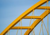 Yellow Steel Arch Of A Bridge Against A Steel Blue Sky. Visible Are The Arch And Girders Of The Brid poster