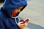 Little Boy  Writes Sms On The Mobile Phone. poster