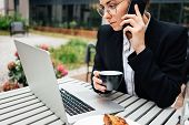 Pensive Business Woman At Cafe Veranda Hold Coffee Cup And Talking Something On Smartphone. Portrait poster
