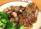 Coq au vin. Chicken casseroled in red wine. Focus on chicken breast.