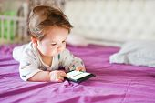 Harm From A Mobile Device To A Child. Toddler Boy Is Lying Looking At The Phone. The Concept Of Depe poster
