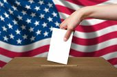 stock photo of ballot-paper  - Hand With Ballot And Wooden Box On Flag Of Usa - JPG