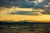 Sundown over the sea and land with mountains on the horizon - Sunset saescape, landscape poster