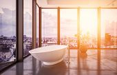 Modern penthouse interior with freestanding bathtub overlooking a city. 3d Rendering poster