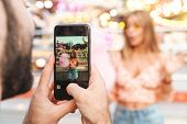 Photo of a man take photo of his shocked emotional woman walking outdoors in amusement park by mobil poster