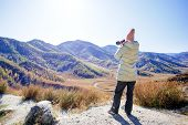 Woman Hiking In Mountains With Camera.  Woman With A Photo Camera Enjoys The Beauty Of Nature Hiking poster