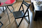 A Black, Wooden Chair In The Middle Of The Kitchen Against A Brown Laminate And Kitchen Furniture: A poster