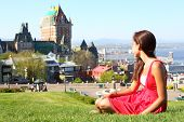 Quebec City scape with Chateau Frontenac and young woman in red summer dress sitting in grass enjoyi