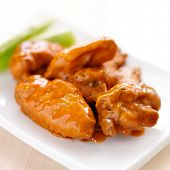 stock photo of nibbling  - plate of buffalo wings with celery closeup - JPG