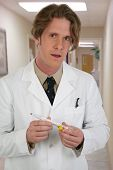 stock photo of rectal  - Man in white lab coat with thermometer in clinic hallway - JPG