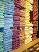 stock photo of shelving unit  - rainbow of colors of towels displayed in a store - JPG
